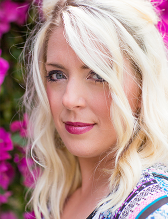 portrait of girl with blonde hair and pink flowers in background outside photograph