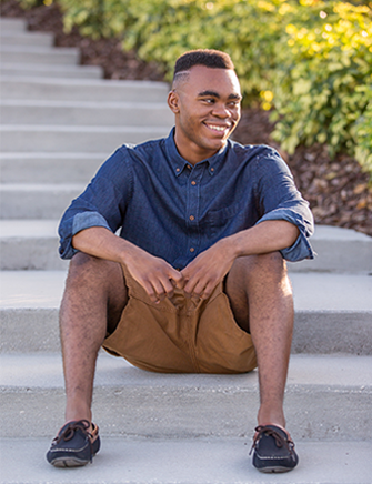 senior portraits on young man sitting on steps in florida