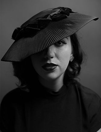 black and white picture of a lady in a black hat in photography studio