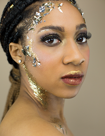 portrait of a young lady with glitter on her face with tan background